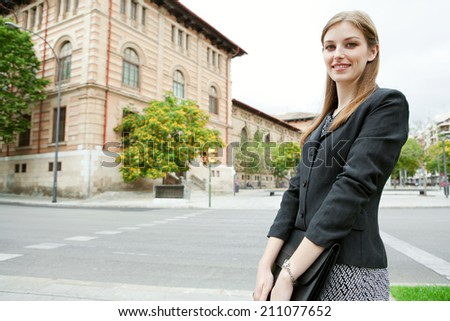 Smiling professional business woman standing in a classic city with stone buildings, smiling at the camera and holding a briefcase folder under her arms. Business people at work, outdoors. - stock photo