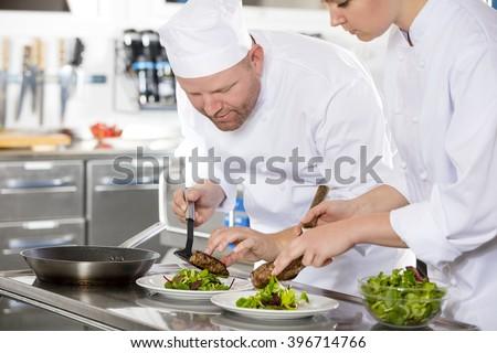 Smiling professional chef prepare steak dish at restaurant - stock photo