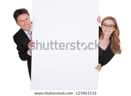 Smiling professional man and woman wearing glasses holding up a blank white sign for your text or advertisement isolated on white - stock photo