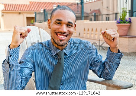 Smiling professionally dressed young man with victory gesture - stock photo
