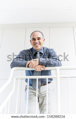 Smiling proud business man standing in office hallway leaning on railing - stock photo