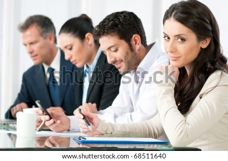 Smiling proud business woman looking at camera with satisfaction and working colleagues in office - stock photo