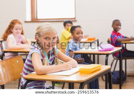 Smiling pupils sitting at her desk at the elementary school - stock photo