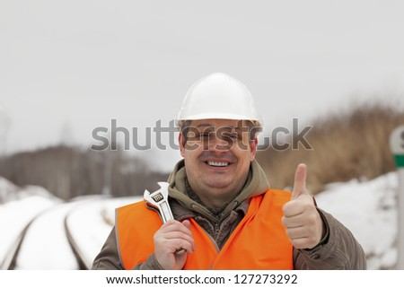 Smiling railroad worker with outstretched hand with thumb up - stock photo