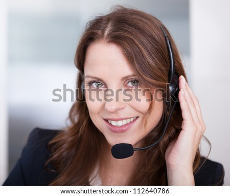 Smiling receptionist or call centre worker sitting typing at a computer while speaking into a headset with a microphone - stock photo