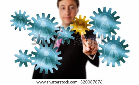 Smiling recruitment consultant is picking a female worker icon embossed on a golden cog in a mission critical position inside a virtual gear train of metallic cogwheels. Cutout isolated on white. - stock photo