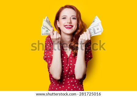 Smiling redhead girl in red dress with money on yellow background. - stock photo