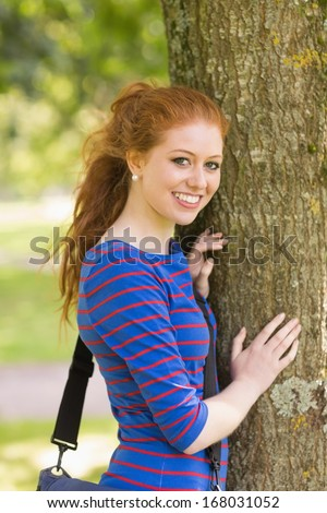 Smiling redhead student leaning on tree looking at camera on college campus