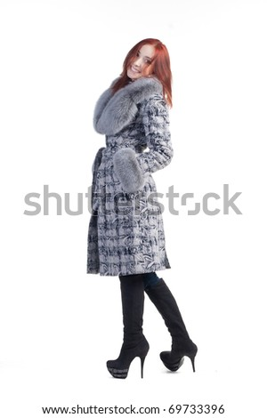 Smiling redhead woman in grey coat isolated on white - stock photo
