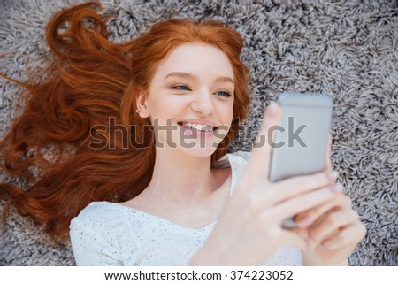 Smiling redhead woman lying on the carpet and using smartphone at home