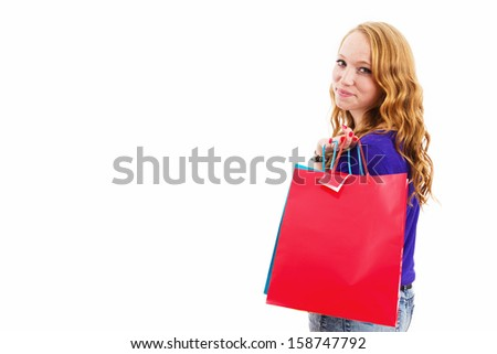 smiling redhead woman with shopping bags on white background with copyspace - stock photo