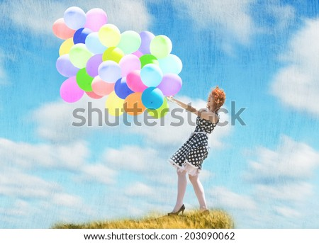 Smiling redheaded girl with balloons in the wind, cloudy sky background