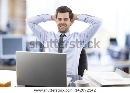 Smiling relaxed businessman leaning back in his chair in front of his desk and laptop in office. He wears shirt and tie. - stock photo