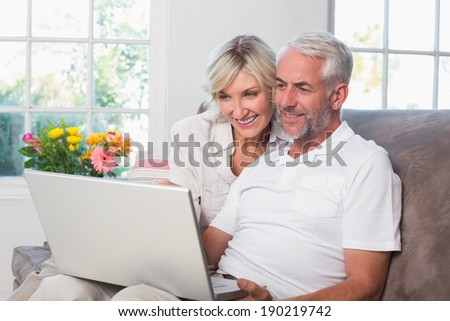 Smiling relaxed mature couple using laptop at home - stock photo