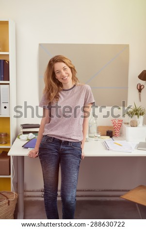 Smiling relaxed young businesswoman in jeans working from home standing sitting on the edge of her desk looking at the camera with a lovely warm smile - stock photo