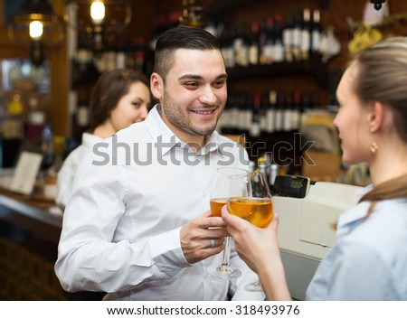 Smiling restaurant visitors waiting for table and drinking wine at bar