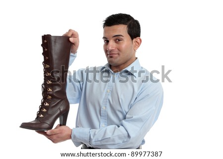Smiling retail salesman holding or showing off a ladies leather boot. - stock photo