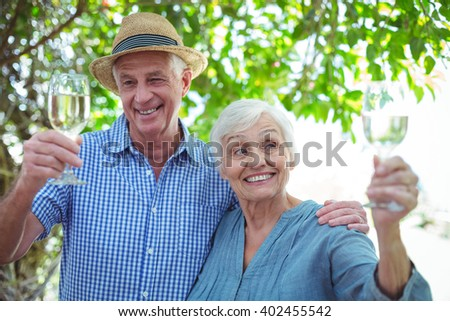 Smiling retired couple holding white wine while standing outdoors - stock photo
