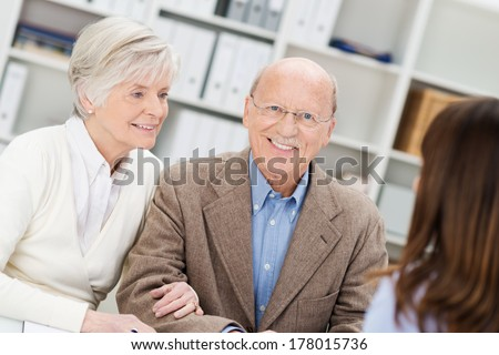 Smiling retired couple in a business meeting getting advice from their insurance broker or financial adviser as they sit in her office - stock photo
