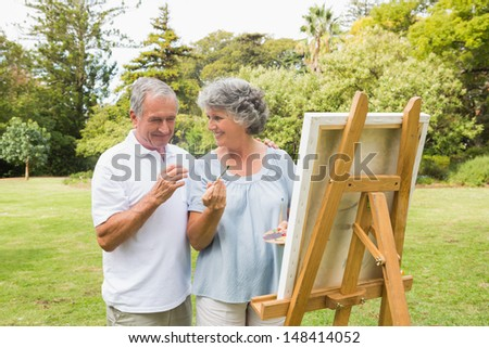 Smiling retired woman painting on canvas with husband and talking in the park - stock photo