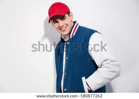 Smiling retro fifties sportive fashion man wearing blue baseball jacket and red cap. Studio shot against white. - stock photo