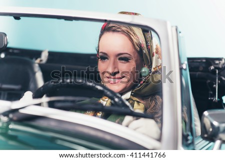 Smiling retro 1960s fashion woman with headscarf driving sports car. - stock photo