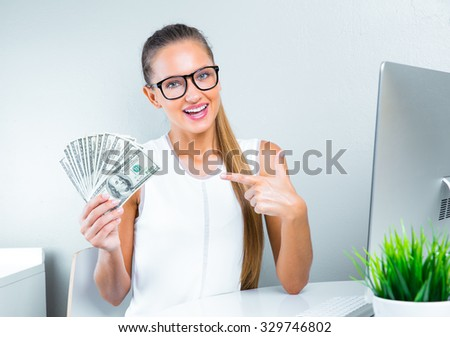 smiling rich business woman holding money on pointing her finger on it. - stock photo