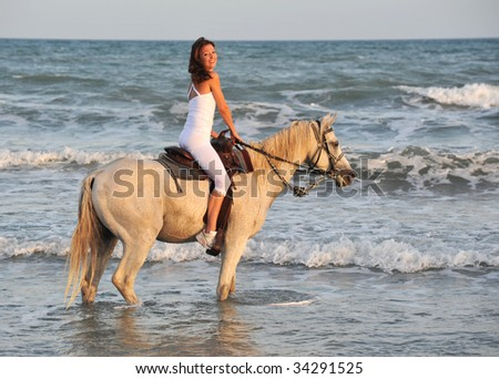 smiling riding young woman in the sea