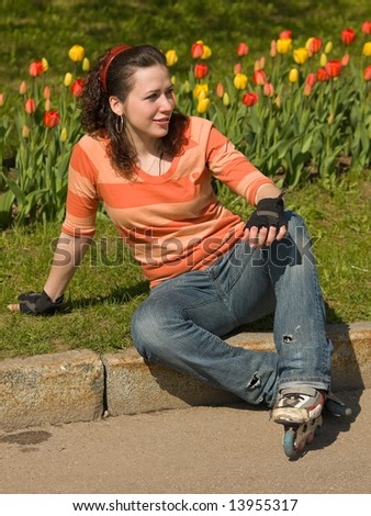 Smiling Rollerskating Girl with Flowers on Background - stock photo