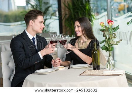 Smiling romantic couple in love is sitting in restaurant together and drinking wine - stock photo