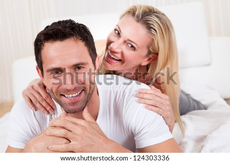 Smiling romantic couple playing on top of the bedclothes with the handsome man smiling directly into the camera - stock photo
