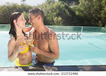Smiling romantic young couple with champagne flutes by swimming pool - stock photo