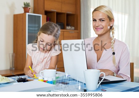 Smiling russian businesswoman browsing internet at home, daughter drawing  in pencil. focus on girl
