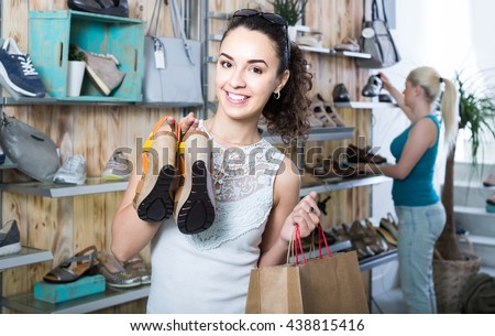 smiling russian girl holding a picked pair of shoes in the boutique - stock photo