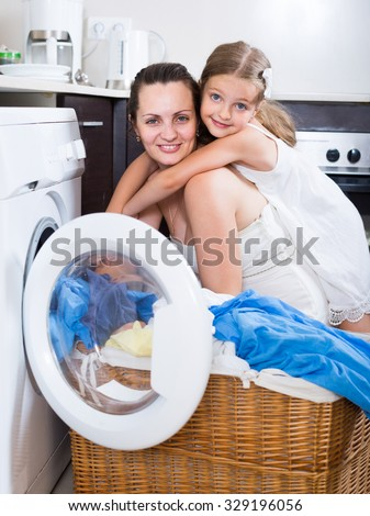 smiling russian  housewife and her daughter with linen near washing machine  - stock photo