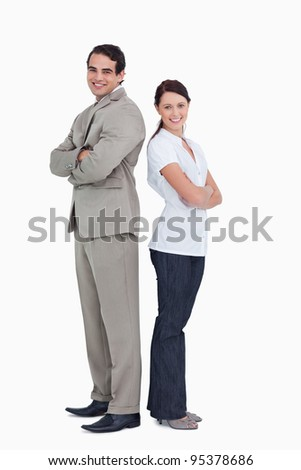 Smiling sales team with arms folded standing back to back against a white background