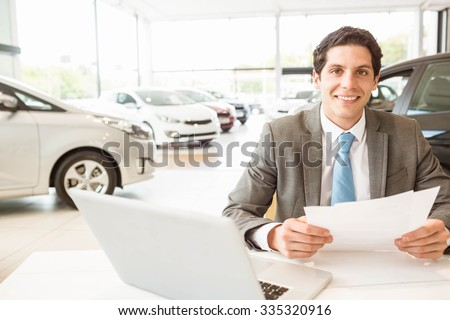 Smiling salesman reading a document at new car showroom - stock photo