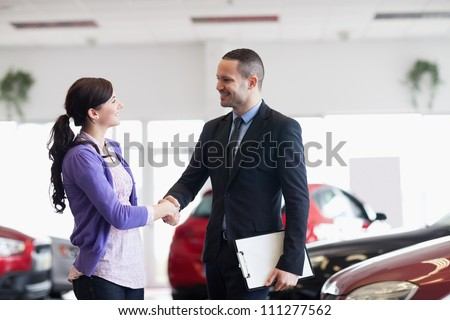 Smiling salesman shaking the hand of a woman in a car shop - stock photo
