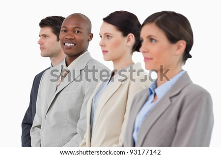 Smiling salesman standing between his associates against a white background