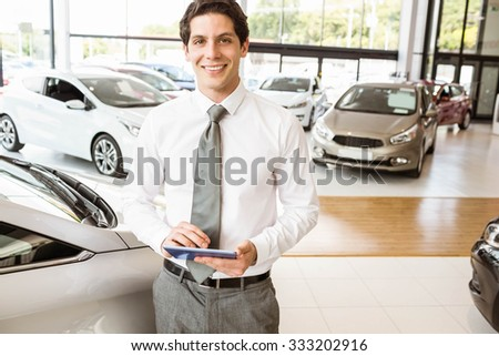 Smiling salesman using tablet near a car at new car showroom - stock photo