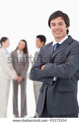 Smiling salesman with arms crossed and team behind him against a white background