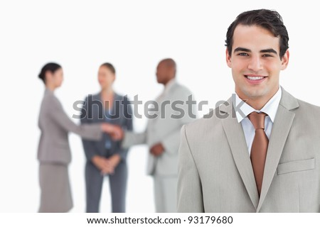 Smiling salesman with businesspeople behind him against a white background - stock photo