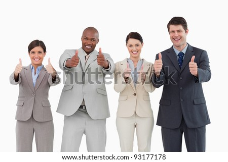 Smiling salesteam giving thumbs up against a white background - stock photo