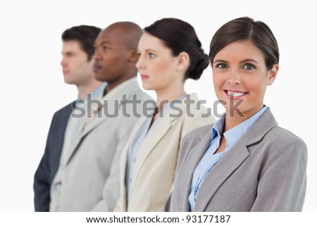 Smiling saleswoman standing next to her associates against a white background
