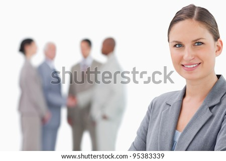 Smiling saleswoman with colleagues behind her against a white background