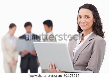 Smiling saleswoman with laptop and colleagues behind her against a white background - stock photo