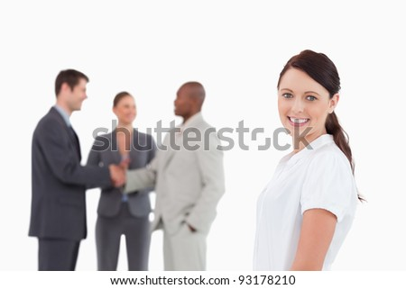 Smiling saleswoman with three colleagues behind her against a white background