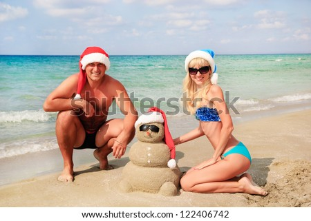 Smiling sandy snowman in red santa hat and young happy couple on the sea beach. Holiday concept can be used for New Year and Christmas Cards - stock photo