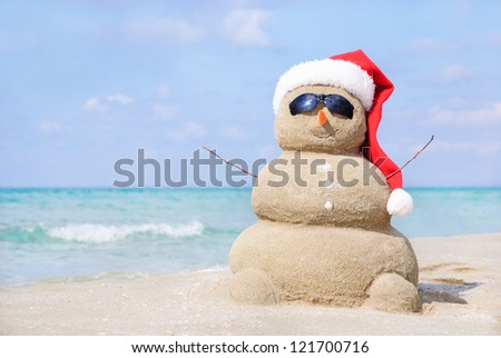 Smiling sandy snowman in red santa hat on the sea beach. Holiday concept can be used for New Year and Christmas Cards - stock photo