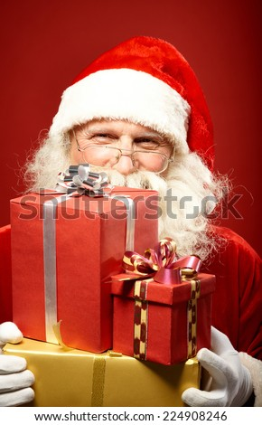 Smiling Santa Claus with pile of gifts - stock photo